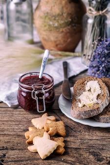 Biscuits faits maison au miel et au sucre, confiture de framboises dans un bocal, pain et beurre, couteau, sur un fond en bois. concept de petit déjeuner.