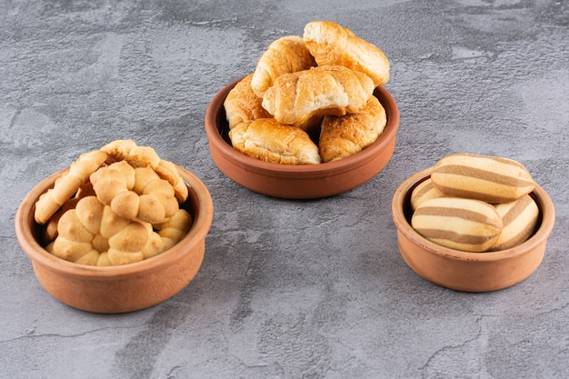 Biscuits faits maison frais dans un bol de poterie sur fond gris.
