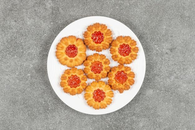 Biscuits faits maison avec de la gelée sur plaque blanche