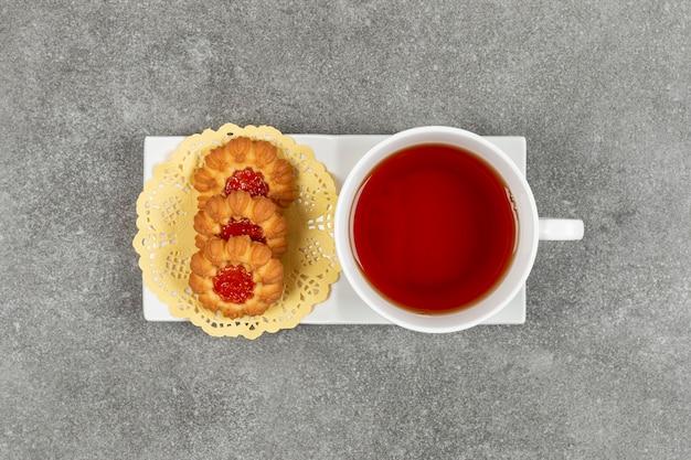 Biscuits faits maison avec de la gelée et une tasse de thé sur une soucoupe blanche
