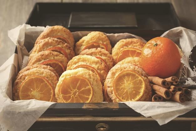 Biscuits faits maison avec des mandarines tranchées et des jouets de noël dans une boîte sombre. image tonique. mise au point sélective.