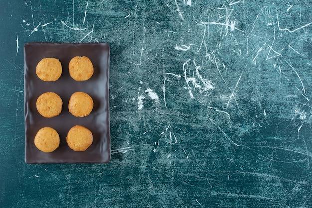 Biscuits faits maison sur une plaque noire, sur fond bleu. photo de haute qualité