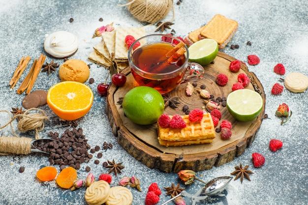 Biscuits à la farine, thé, fruits, épices, choco high angle view sur planche de bois et fond de stuc