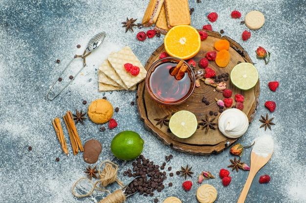 Biscuits à la farine, thé, fruits, épices, choco, passoire sur planche de bois et fond de stuc, vue de dessus.