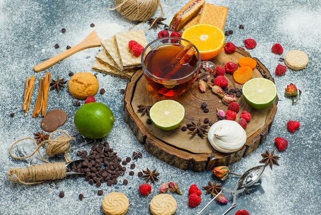 Biscuits à la farine, thé, fruits, épices, choco, passoire à plat sur planche de bois et fond de stuc