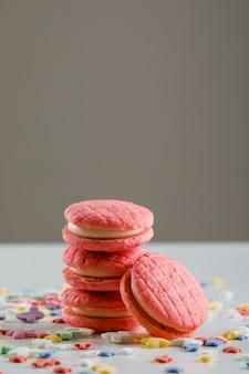 Biscuits de fête avec des pépites de sucre sur une table blanche et grise,