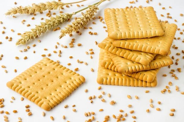 Biscuits de forme carrée sur un tableau blanc. épis et grains de blé