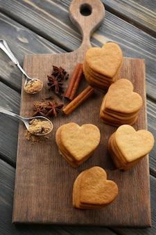 Biscuits en forme de coeur et cannelle sur planche à découper
