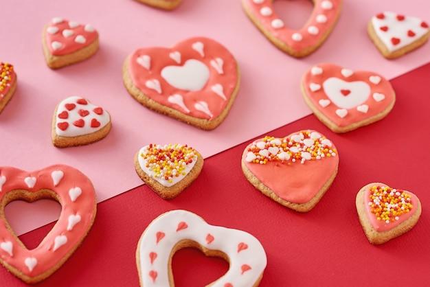 Biscuits en forme de coeur décorés sur de couleur rouge et rose