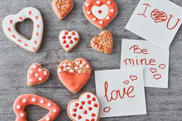 Biscuits en forme de coeur déocrated et feuilles de papier avec des inscriptions soyez à moi, amour et je t'aime sur gris. concept de la saint-valentin