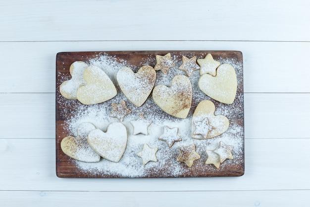 Biscuits en forme de coeur et étoiles sur une planche à découper en bois sur un fond de planche de bois blanc. pose à plat.