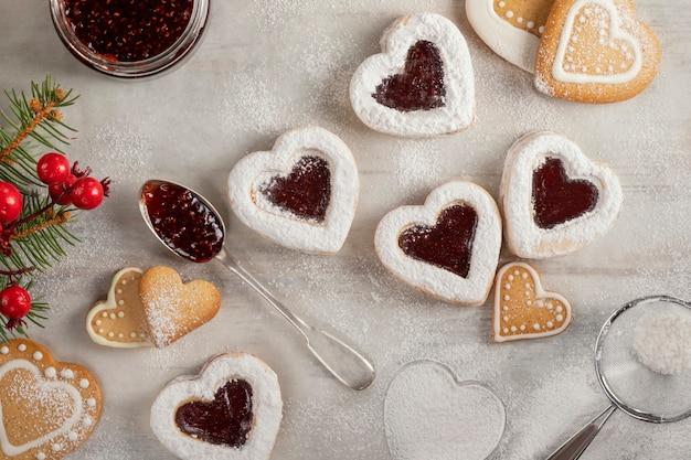Biscuits en forme de coeur faits maison avec de la confiture de framboises sur une table en bois blanc pour noël ou la saint-valentin. vue de dessus.