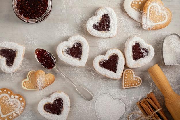 Biscuits en forme de coeur faits maison avec de la confiture de framboises sur une table en bois blanc pour noël ou la saint-valentin.