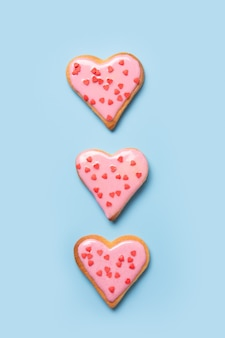 Biscuits en forme de coeur faits maison sur tableau blanc.