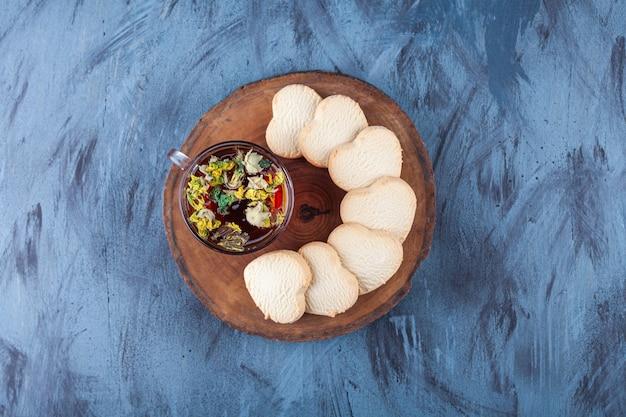 Biscuits en forme de coeur frais parfumés et tasse de tisane sur morceau de bois.