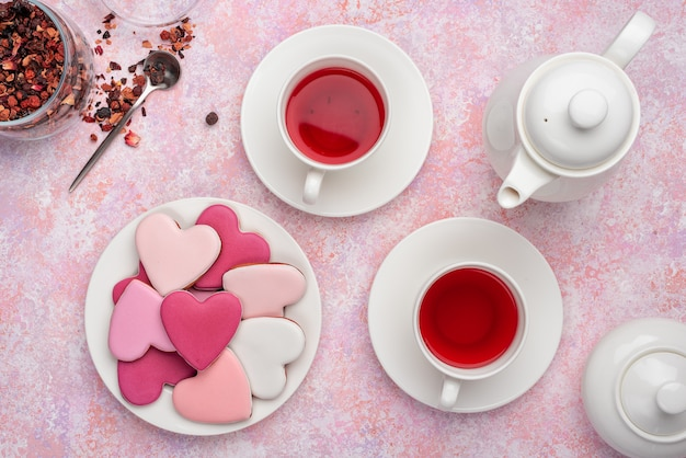 Biscuits en forme de coeur avec glaçage au thé aux baies. concept: tea party de la saint-valentin, table de fête en rose.