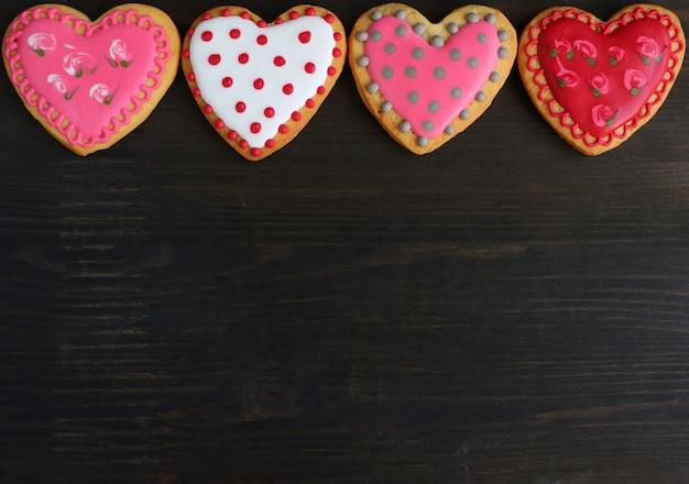 Biscuits en forme de coeur avec un glaçage royal magnifique sur fond de bois noir