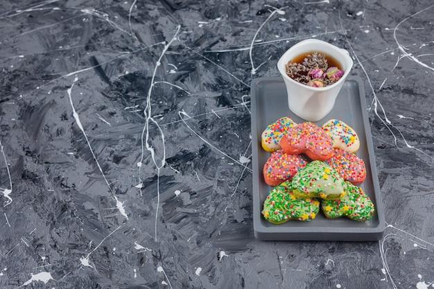 Biscuits en forme de coeur avec des paillettes colorées et une tasse de thé noir.