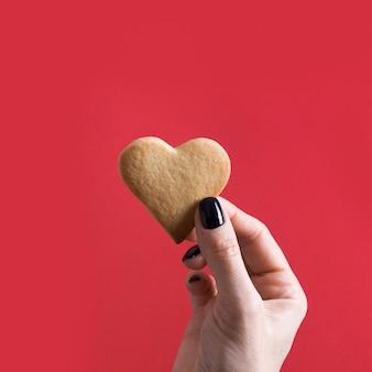 Biscuits en forme de coeur pour la saint-valentin en main féminine sur rouge. concept.