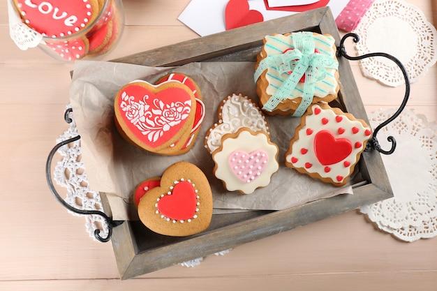 Biscuits en forme de coeur pour la saint valentin sur plateau sur table en bois de couleur