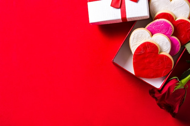 Biscuits en forme de coeur pour la saint-valentin et roses dans une boîte cadeau rouge, vue de dessus