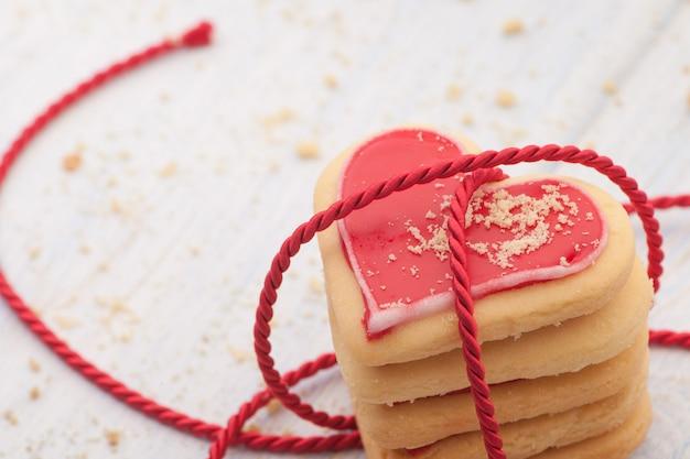 Biscuits en forme de coeur rouge dans la bande connectée sur des planches de bois en gros plan le jour de la saint-valentin
