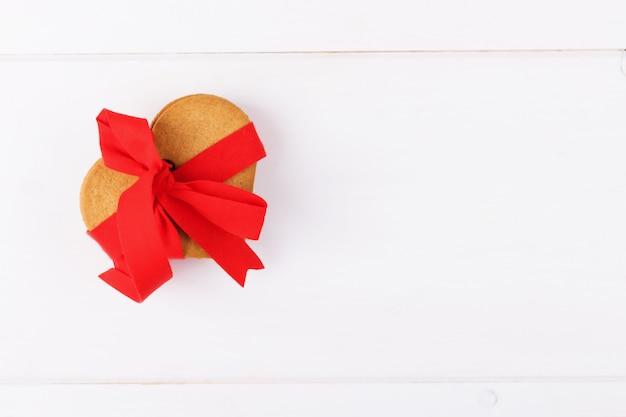 Biscuits en forme de coeur avec ruban rouge, cadeau comestible sur fond blanc. symbole d'amour douillet et fond de saint valentin et festif, carte de voeux