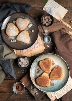 Biscuits en forme de cœur saupoudrés de cacao et de sucre en poudre. la vue du haut.