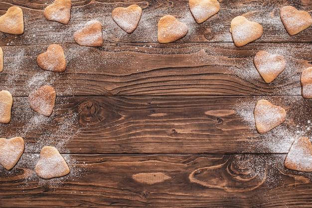 Biscuits en forme de cœur saupoudrés de sucre en poudre sur une table en bois