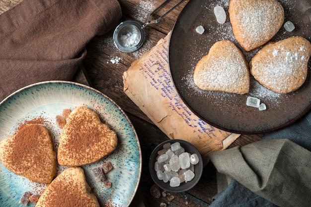 Les biscuits en forme de cœur sont saupoudrés de cacao et de sucre en poudre sur un fond vintage.