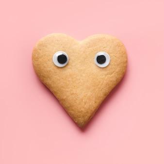Biscuits en forme de coeur avec des yeux pour la saint-valentin sur rose. concept alimentaire. vue d'en-haut.