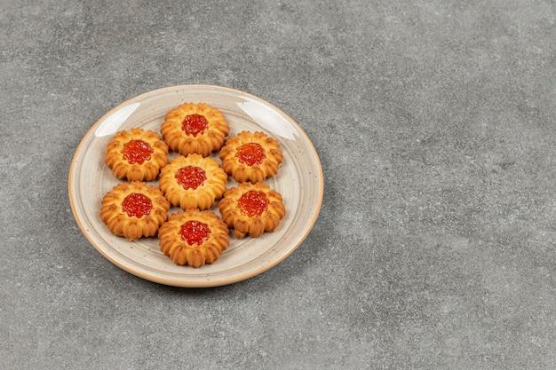 Biscuits en forme de fleur avec de la gelée sur plaque en céramique