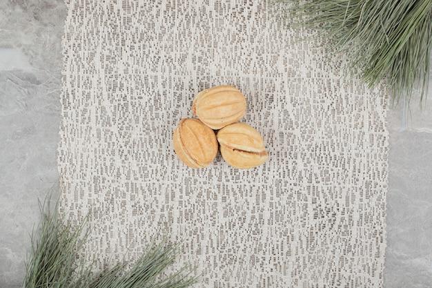 Biscuits en forme de noix sur toile de jute avec branche. photo de haute qualité