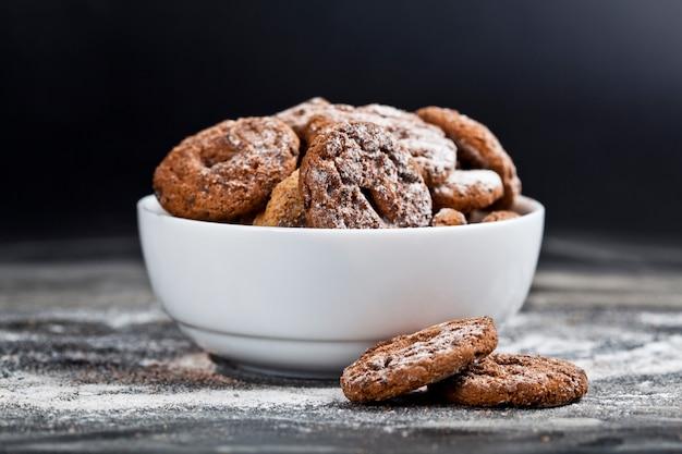 Biscuits frais aux pépites de chocolat et à l'avoine cuits au four avec du sucre en poudre dans un bol blanc