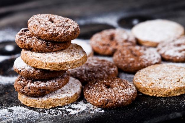 Biscuits frais aux pépites de chocolat et à l'avoine avec une pile de sucre en poudre
