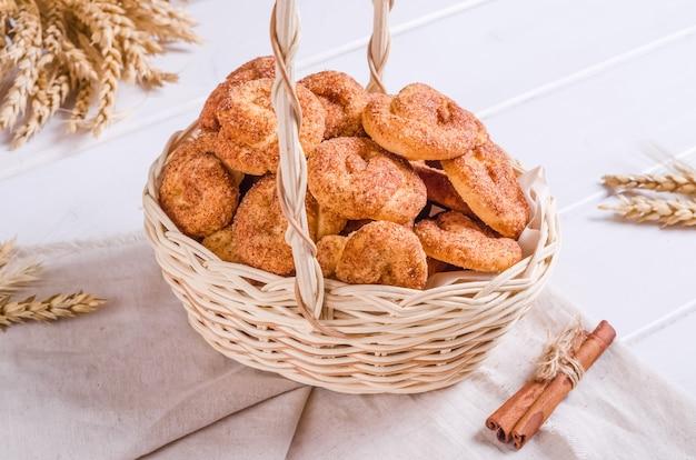Biscuits frais et savoureux à la cannelle dans un panier en osier sur fond de bois blanc