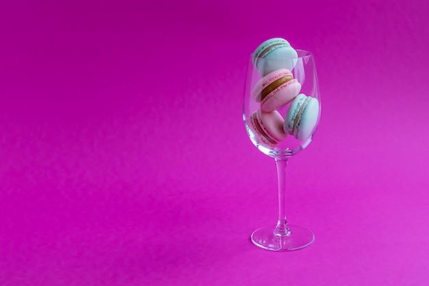 Biscuits français macarons dans un gobelet en verre sur un fond rose.