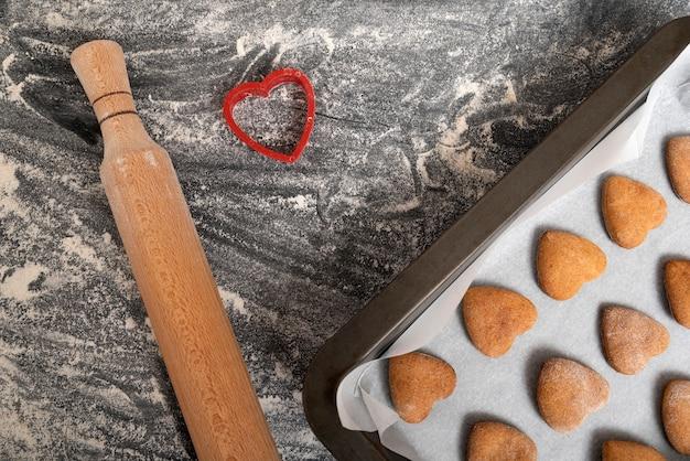 Biscuits frites fraîchement sortis du four avec de la farine et un rouleau à pâtisserie tiré par le haut sur une plaque à pâtisserie