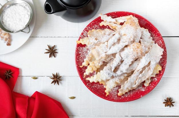 Biscuits frits croustillants de broussailles dans du sucre en poudre avec du thé et de la confiture