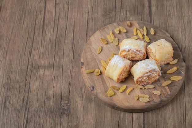 Biscuits frits avec des raisins secs jaunes et du sucre en poudre sur le dessus.