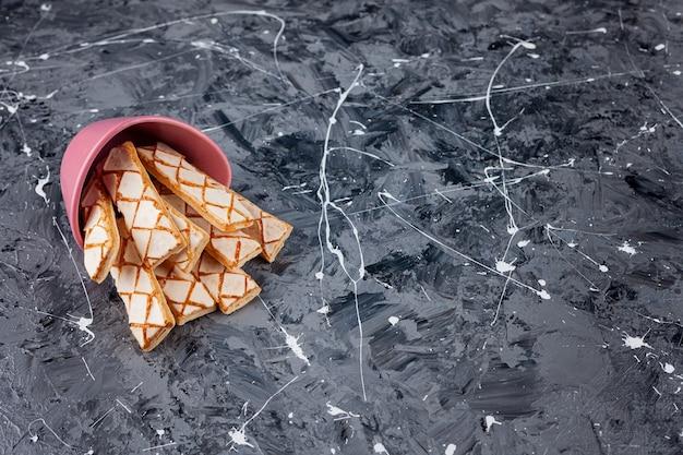 Biscuits gaufres éparpillés dans un seau rose.