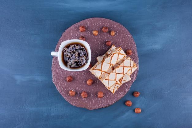 Biscuits gaufres éparpillés avec une tasse de tisane.