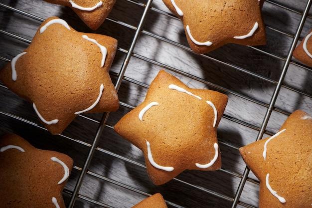 Biscuits ginder en forme d'étoile fraîchement cuits sur une grille de refroidissement. gros plan, vue de dessus.
