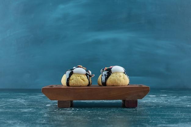 Biscuits glacés faits maison sur une plaque en bois, sur fond bleu. photo de haute qualité