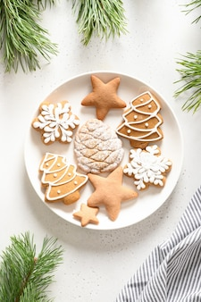 Biscuits glacés à la main de noël dans la plaque décorée de branches de sapin sur fond blanc. vue d'en-haut. format vertical.