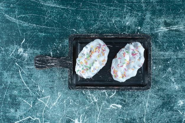 Biscuits glacés sur une planche, sur la table bleue.
