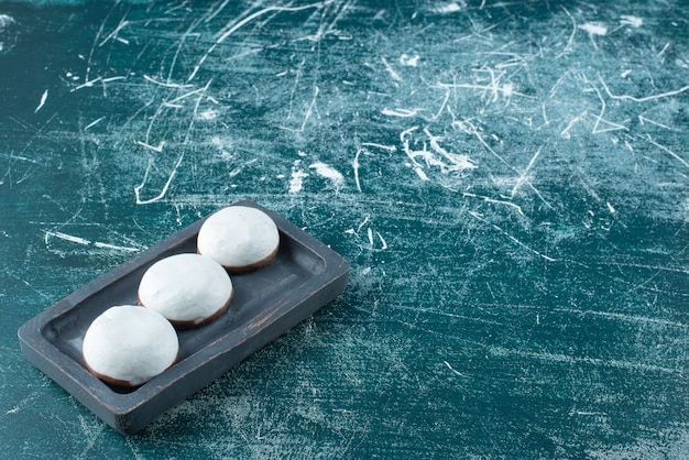 Biscuits glacés ronds sur plaque noire.