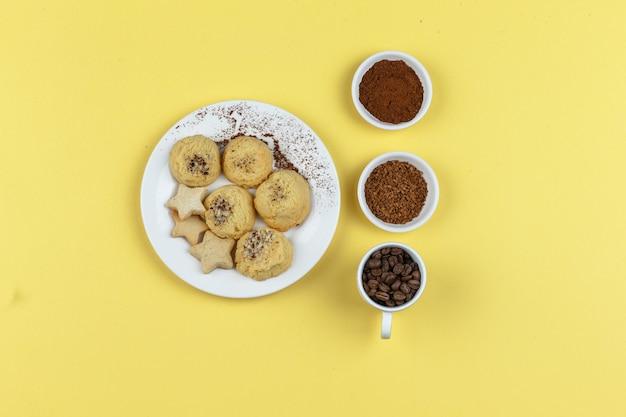 Biscuits et grains de café sur fond jaune