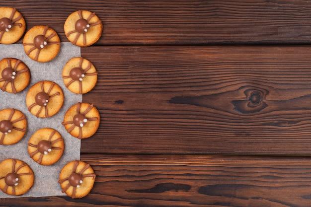 Biscuits d'halloween avec des décorations drôles sur une table de cuisine en bois, espace copie
