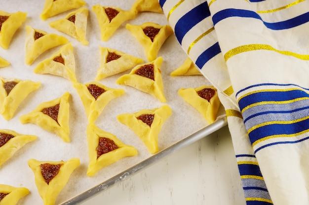 Biscuits hamantaschen crus sur une plaque à pâtisserie avec tallit